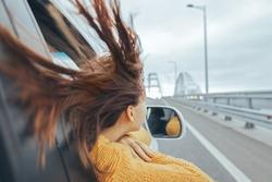 Rear view of pre teen girl in car looking forward on a bridge at weekend road trip
