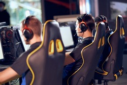 Rear view of professional cyber sport gamers wearing headphones participating in  tournament