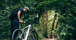 Rear view of professional male cyclist cycling on mountain road on nature background. Male bicyclist riding a bike in the forest outdoor.