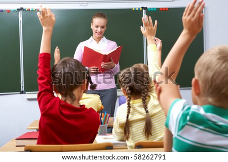 Rear view of pupils raising arms during the lesson with teacher looking at them