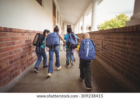 Rear view of pupils walking at corridor in school