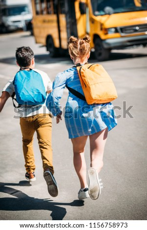 rear view of pupils with backpacks running to school bus #1156758973
