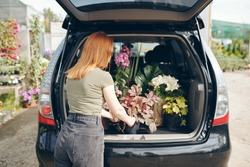 Rear view of redhead woman in tshirt and jeans standing by open trunk and loading flowers into car after shopping at flower market