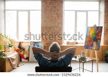Rear view of restful professional painter sitting in armchair with his hands behind head in studio of arts