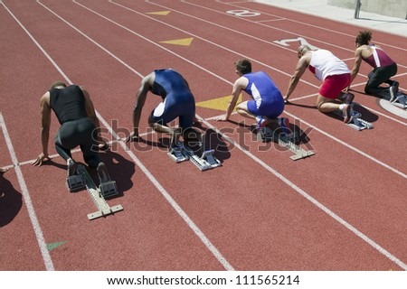 Rear view of runners preparing for race at starting blocks