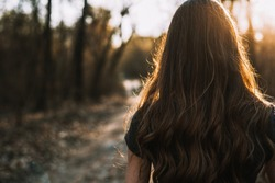 Rear view of sad young woman walking through park at sunset