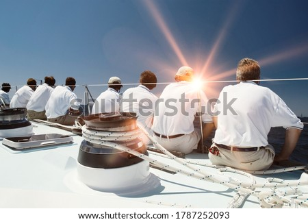 Rear view of sailing crew with lens flare Stockfoto ©