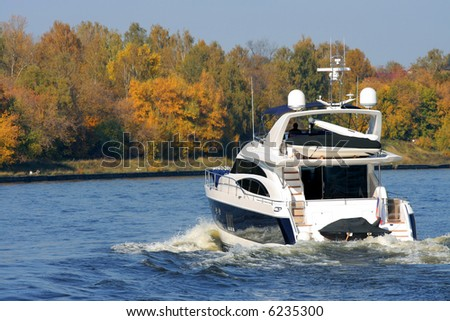 Rear view of sailing luxury yacht on golden autumn scenic background.