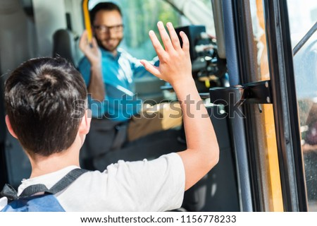 rear view of schoolboy waving to happy bus driver while entering bus