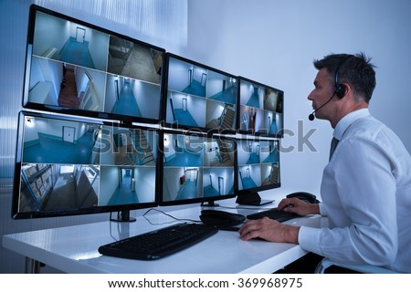 Rear view of security system operator looking at CCTV footage at desk in office Сток-фото ©