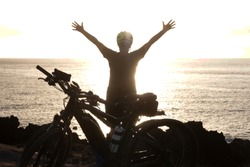 Rear view of senior active woman in front to the ocean at sunset. Black silhouette. Arms raised. Freedon and happiness concept. Yellow helmet.  Electric bici for a healthy lifestyle
