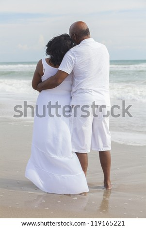 Rear view of senior African American man and woman couple on a deserted tropical beach