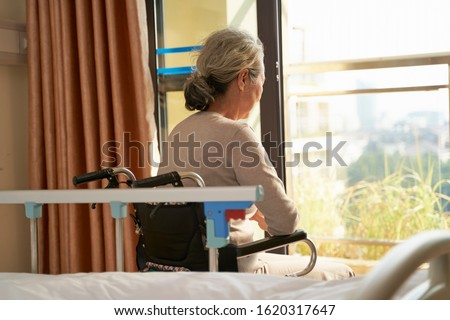 rear view of senior asian woman sitting in wheel chair in nusing home or hospital ward  in front of window
