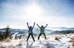 Rear view of senior couple hikers in snow-covered winter nature, jumping.