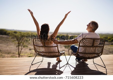 Rear view of senior couple sitting on chairs at the resort #715608223