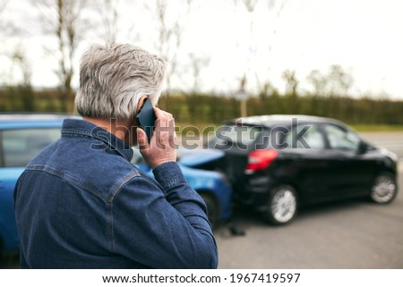 Rear view of senior male driver standing by damaged car after traffic accident reporting incident to insurance company using mobile phone Photo stock ©