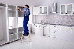 Rear View Of Serviceman Standing On Ladder Fixing Cabinet Door In Modular Kitchen