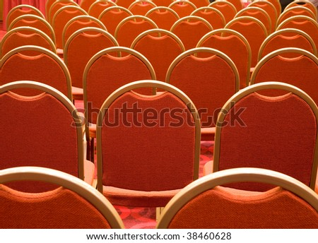 Rear view of several rows of red armchairs in conference hall