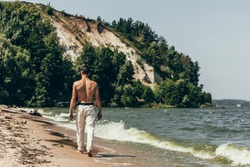 rear view of shirtless man walking by sandy beach