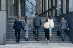 Rear view of Six Business People Walking up the Stairs. Men and women in formal suits going up stairs into office building. Partnership, communication business people concept.