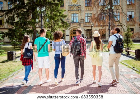 Rear view of six students, bachelor`s campus life rhythm. They are walking after to college building and discuss the project, gesturing, sharing the ideas Stock photo ©