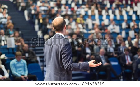 Rear view of speaker giving a talk on corporate business conference. Unrecognizable people in audience at conference hall. Business and Entrepreneurship event.