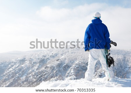 Rear view of sportsman with snowboard watching the nature