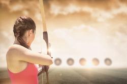 Rear view of sportswoman doing archery on a sports field