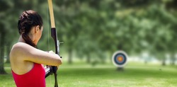 Rear view of sportswoman doing archery on a white background against park on sunny day