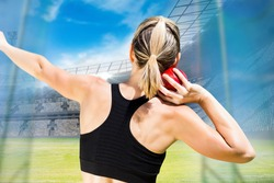 Rear view of sportswoman is practising shot put against view of a stadium