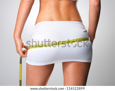 Rear view of sporty woman with slim body measuring hips - model posing in studio