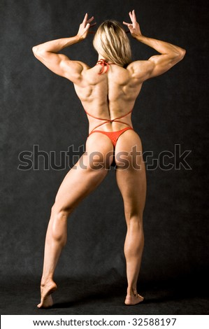 Rear view of strong female in red bikini against black background