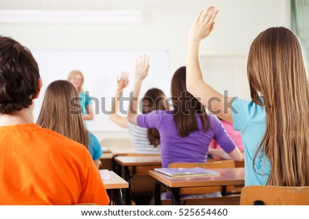 Rear view of students in bright classroom responding to the teacher\'s question, raising their arms up.