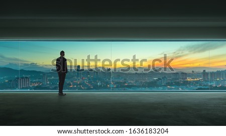Rear view of successful businessman looking the city from his office , early morning scene  .