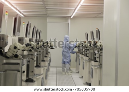 Rear View of technician in clean suits he is teaching a new technician in a semiconductors manufacturing facility ,select focus ,blurred background
