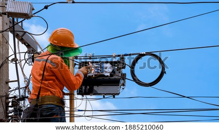 Rear view of technician on wooden ladder checking fiber optic cables in internet splitter box on electric pole against blue sky background