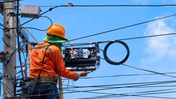 Rear view of technician on wooden ladder is installing fiber optic and internet splitter box on electric pole against blue sky background