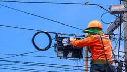 Rear view of technician on wooden ladder is working to install fiber optic and splitter box on electric pole against blue sky background