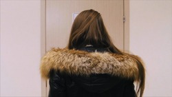 Rear view of the girl in the winter jacket standing opposite the door upset and angry. girl stands opposite the door of the office and does not understand why it is closed. Back view of woman thinking