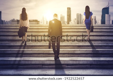 Rear view of three business people carrying suitcase while climbing stairs toward bright modern city background Foto stock ©