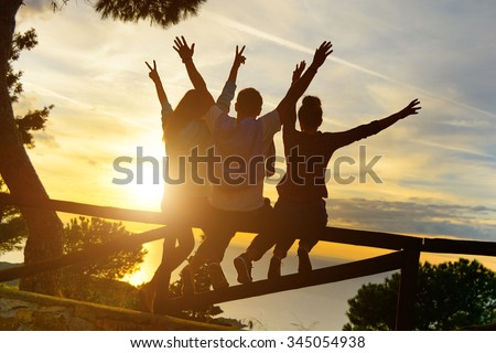 Rear view of three couple best friends travelers put hands up at sunset. Young  relaxing hipster wanderers enjoying exclusive alternative destination. Holiday life moment at warm orange light #345054938