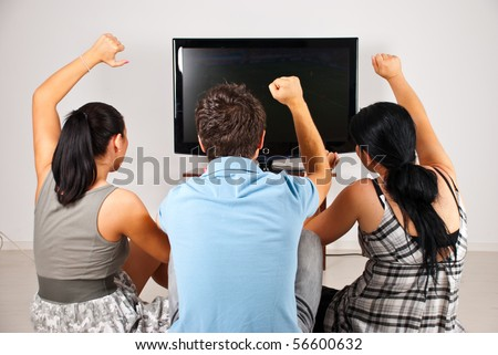 Rear view of three excited  soccer fans sitting on floor and  watching favorite team goal  at tv