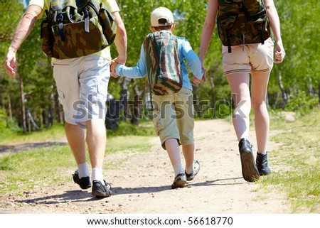 Rear view of three family members going down forest path during summer vacation