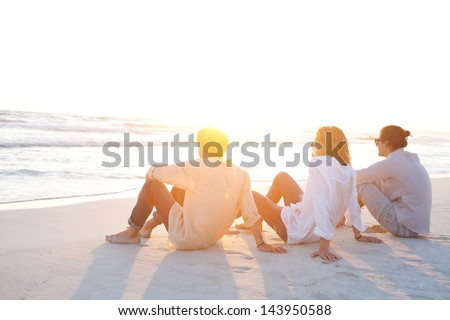 Rear view of three friends men sitting together on a white sand beach with the sun setting behind them with warm orange light, during their vacation in an idyllic nature scene destination.