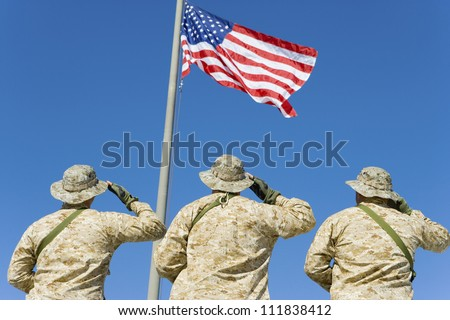 Rear view of three soldiers saluting an American flag