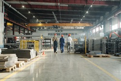 Rear view of three technicians or engineers of industrial plant in workwear leaving workshop at the end of working day