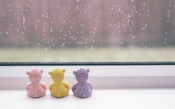 Rear view of three teddy bear sitting next to window  with rain drops in the rainy day, Group of sad teddy sitting together looking out of window watching rain outside,retro filte,love or Sad concept