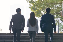 rear view of three young successful asian business people ascending steps