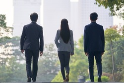 rear view of three young successful asian business people walking on street