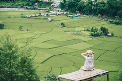 Rear view of tourist woman looking to beautiful rice paddy field in Sapan village a small village nestled in a forested northern valley of pure air and pristine rivers in Nan province of Thailand.